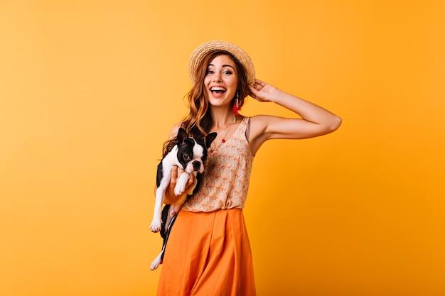 Замечательная рыжая девушка в летней шляпе, выражая счастье во время портретной съемки с собакой. удивительная красивая девушка держит бульдога и улыбается.