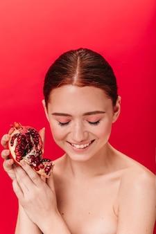 Замечательная рыжая девочка с гранатом смеется с закрытыми глазами. студия сняла блаженную молодую женщину, позирующую со спелым гранатовым деревом.
