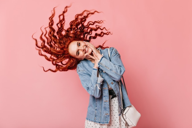 분홍색 배경에 춤 멋진 생강 여자입니다. 스튜디오에서 재미 데님 재킷에 화려한 red-haired 소녀.