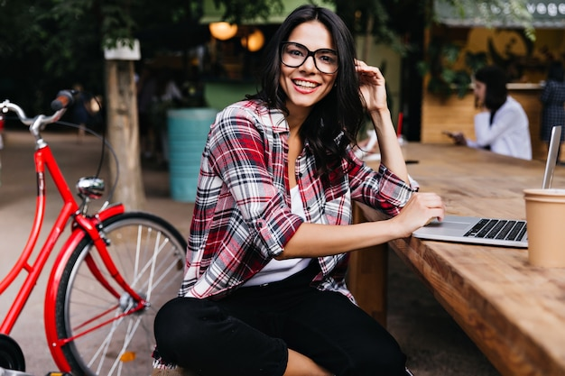 Wonderful girl in good mood sitting on city with laptop and smiling. outdoor portrait of attractive brunette lady in glasses posing beside bicycle.