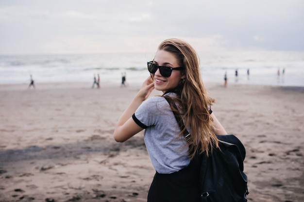 砂浜に立っている間、肩越しに見ている黒いサングラスの素晴らしい女の子。自然にポーズをとるブラックパックと美しい女性モデルの写真。