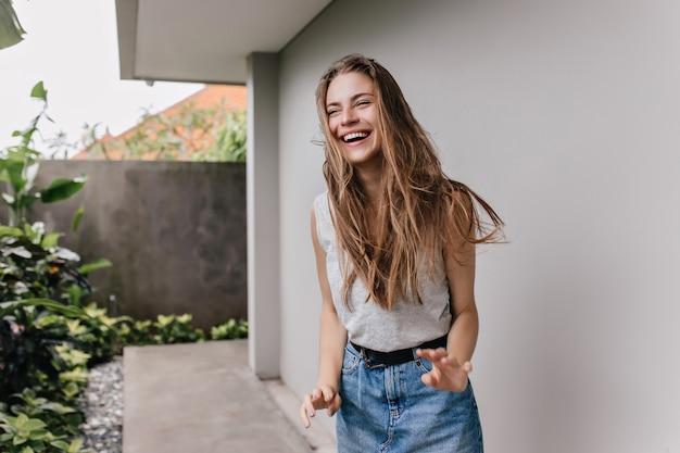 Замечательная девушка в джинсовой юбке смеется и смотрит в сторону. наружное фото красивой кавказской дамы с блестящими волосами дурачится.