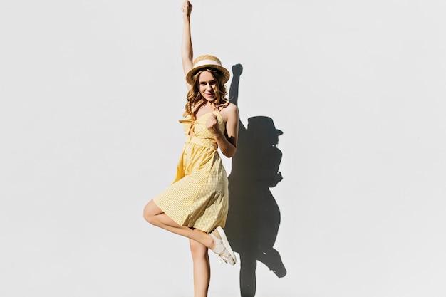 한쪽 다리에 서있는 빈티지 복장에 멋진 여자. 화창한 날에 춤추는 노란색 옷에 쾌활 한 곱슬 여자.