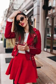 Splendida ragazza in abito rosso che guarda alla telecamera attraverso occhiali scuri