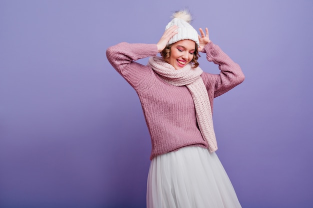 Splendida ragazza in elegante gonna bianca in posa con piacere sulla parete viola. carina giovane donna dai capelli corti con cappello e sciarpa sorridente con gli occhi chiusi.