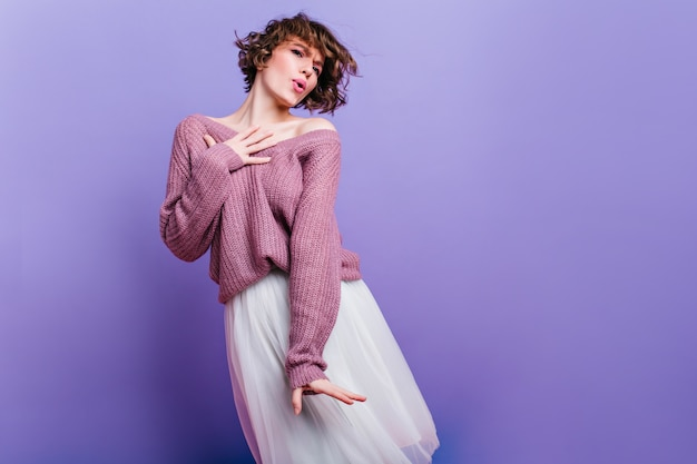 Splendida ragazza in gonna rigogliosa vintage che balla durante il servizio fotografico. foto del modello femminile caucasico soddisfatto con capelli scuri corti in posa sulla parete luminosa.