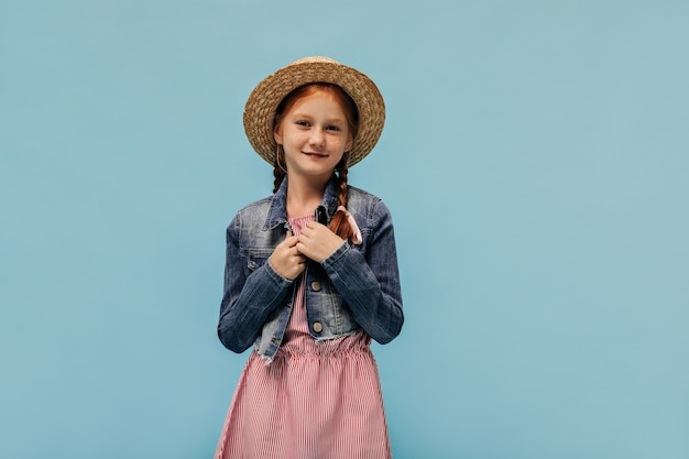 Wonderful girl with freckles and red hair in denim jacket, cool hat and trendy dress looking at front on blue wall