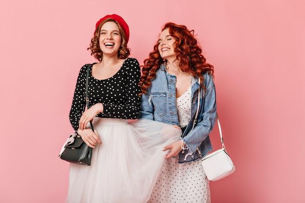 ピンクの背景に浮気する素晴らしい女の子。一緒に笑っているスタイリッシュな白人女性のスタジオショット。