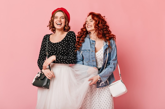 Wonderful girls fooling around on pink background. studio shot of stylish caucasian ladies laughing together.