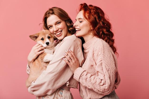 분홍색 배경에 고립 된 귀여운 강아지를 들고 멋진 여자. 애완 동물과 함께 포즈를 취하는 웃는 유럽 숙녀의 스튜디오 샷.