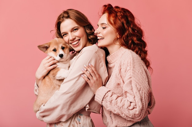 Wonderful girls holding cute dog isolated on pink background. studio shot of smiling european ladies posing with pet.