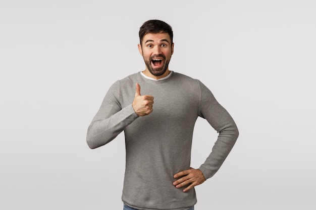 Wonderful idea, lets do it. excited, cheerful, supportive bearded adult man in grey sweater, give positive feedback, adore something really good, show thumb-up approval, like or enthusiastic gesture