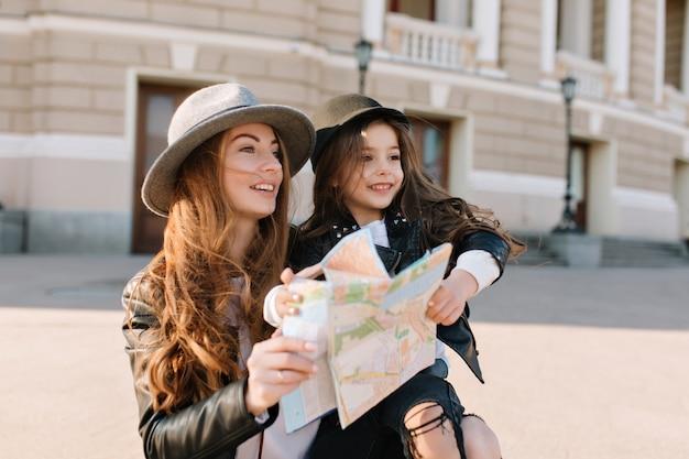 Meravigliosa donna riccia ispirata con cappello che tiene bella figlia e mappa della città, guardando lontano. ritratto all'aperto di due ragazze che viaggiano intorno a un posto nuovo e alla ricerca di luoghi meravigliosi