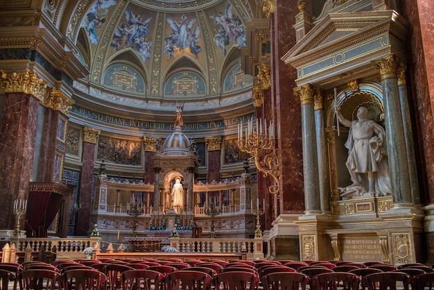 헝가리 부다페스트의 벽과 대리석 조각상 및 조각에 화려한 그림이 있는 가톨릭 대성당의 멋진 내부.