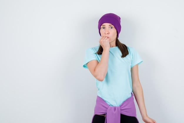 Meravigliosa signora in camicetta, berretto che tiene il pugno sul mento e sembra spaventata, vista frontale.