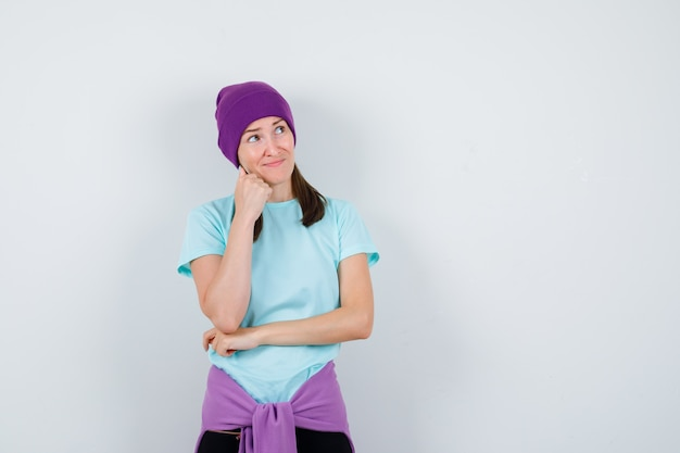 Meravigliosa signora in camicetta, berretto che tiene la mano sul mento e sembra sicura, vista frontale.