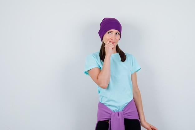 Meravigliosa signora in camicetta, berretto che tiene la mano sul mento e sembra pensierosa, vista frontale.