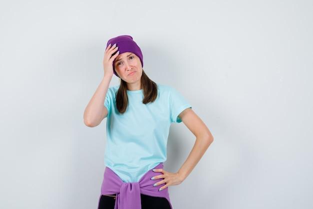 Meravigliosa signora in camicetta, berretto che tiene la mano sulla testa e sembra addolorata, vista frontale.