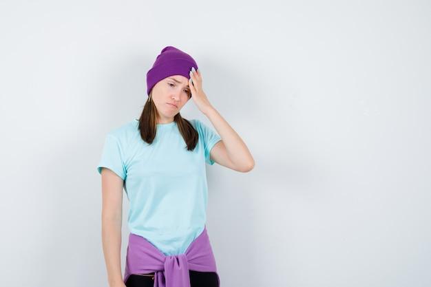 Meravigliosa signora in camicetta, berretto che tiene la mano sulla testa e sembra sconvolta, vista frontale.