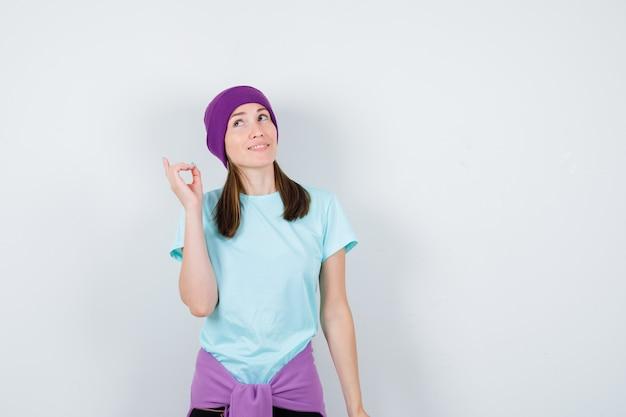 Meravigliosa signora in camicetta, berretto che punta verso l'alto e sembra interessata, vista frontale.