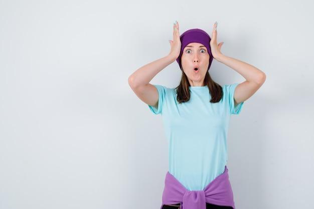 Meravigliosa signora in camicetta, berretto con le mani sulla testa e dall'aspetto scioccato, vista frontale.