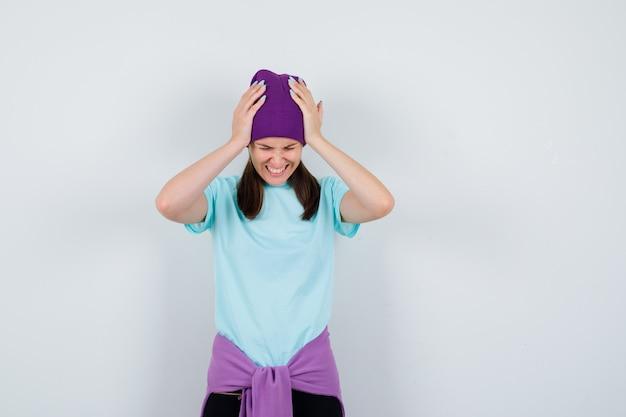 Meravigliosa signora in camicetta, berretto con le mani sulla testa e dall'aspetto stressato, vista frontale.