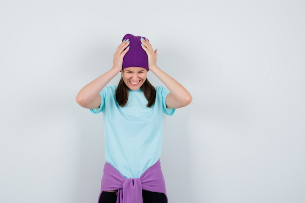 블라우스를 입은 멋진 여성, 머리에 손을 얹고 스트레스를 받고 있는 비니, 전면 전망.