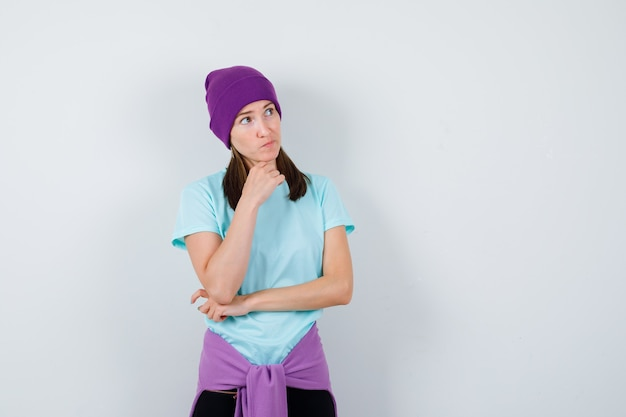 Meravigliosa signora che tiene la mano sotto il mento in camicetta, berretto e sembra pensierosa, vista frontale.