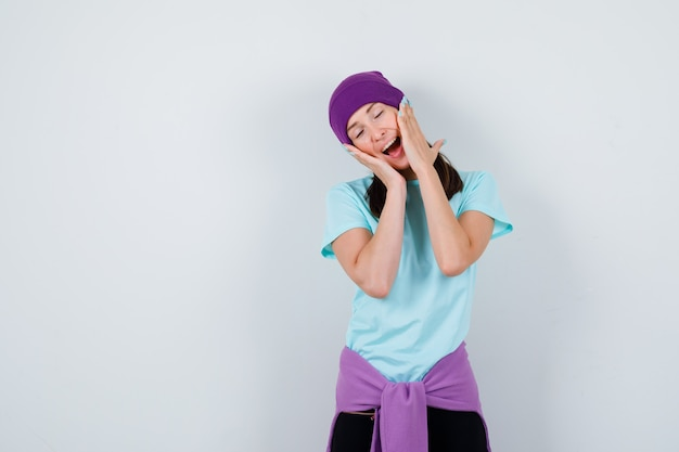 Meravigliosa signora che tiene le mani sulle guance, apre la bocca in camicetta, berretto e sembra felice. vista frontale.