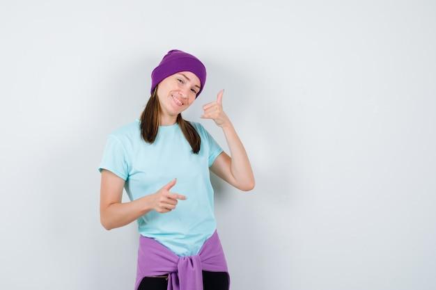 Замечательная дама показывает жест телефона в блузке, шапочке и выглядит весело, вид спереди.