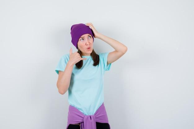 Замечательная дама показывает жест телефона в блузке, шапочке и выглядит удивленно. передний план.