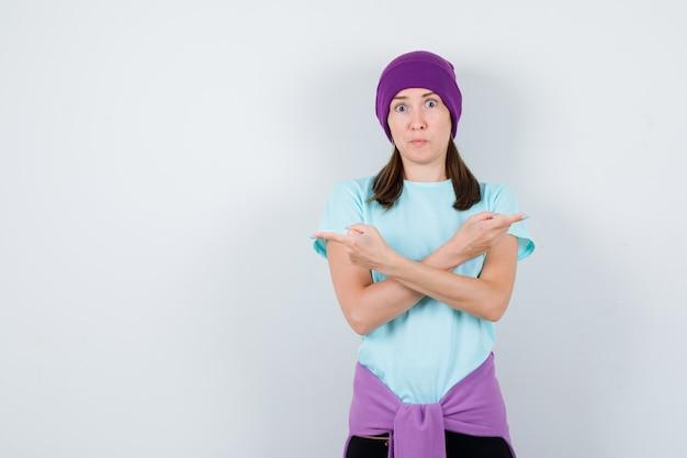 Meravigliosa signora che allarga i palmi delle mani in camicetta, berretto e sembra scioccata. vista frontale.