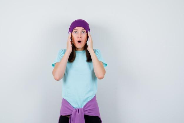 Meravigliosa signora con le mani sulla testa in camicetta, berretto e dall'aspetto scioccato. vista frontale.