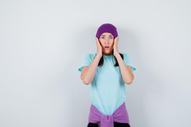 Meravigliosa signora con le mani sulla testa in camicetta, berretto e dall'aspetto terrorizzato, vista frontale.