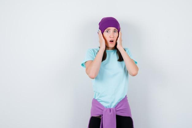 Meravigliosa signora con le mani sulla testa, aprendo la bocca in camicetta, berretto e guardando terrorizzata, vista frontale.