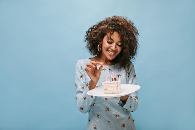 Meravigliosa signora con acconciatura ondulata alla moda in orecchini e vestito blu brillante che sorride e tiene in mano un pezzo di torta con candele sulla parete blu..