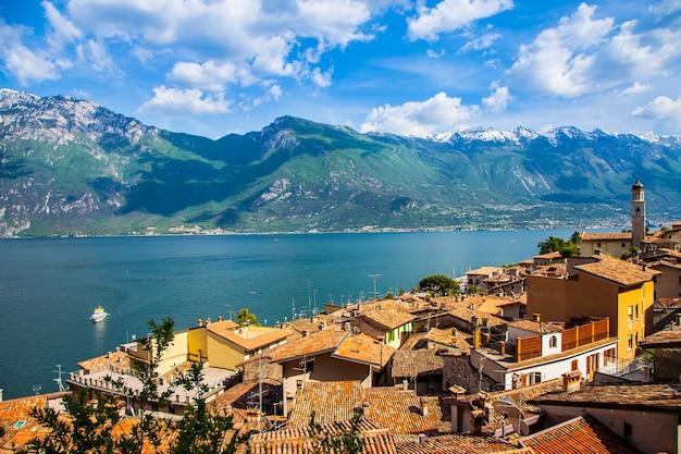 Чудесное озеро италии лаго ди гарда. прекрасный панорамный вид на деревню лимоне-суль-гарда и горы