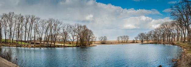 멋진 풍경, 작은 호수에 이른 봄, 파노라마. 갈대, 하늘과 물 속에서 나무의 반영