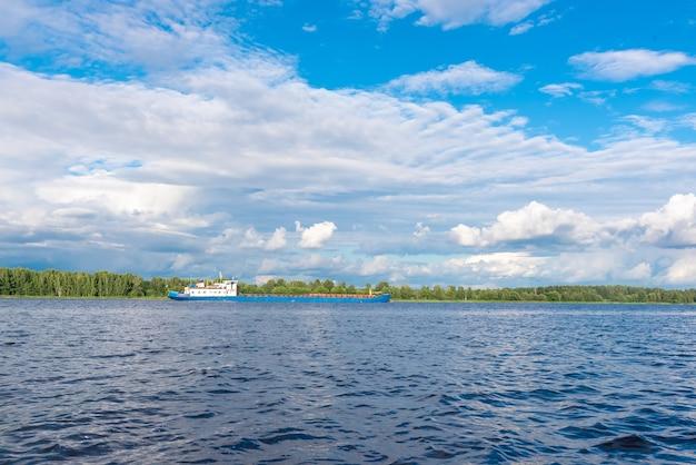 素敵な晴れた夏の日に、ふわふわの白い雲と明るい青空の下で波打つ表面を持つ青い静かな空の川の表面を持つ素晴らしい風景。
