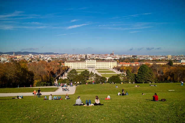Wonderful landscape with view to schonbrunn palace in vienna, austria and green wide grass field with sitting and relaxing people on a ground on a blue sky background.