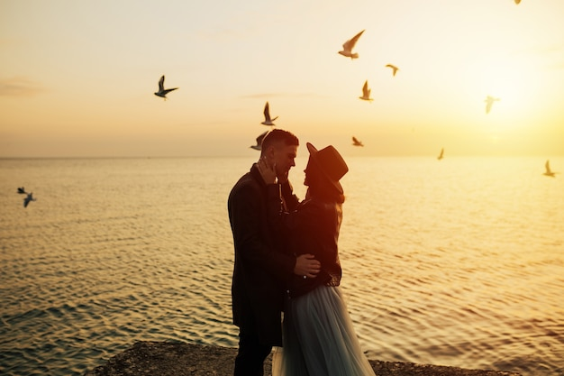 Wonderful landscape with young tourist couple at golden sunset and flying seagulls on beach.