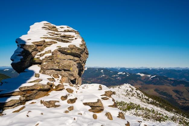 カルパティア山脈の大きな岩だらけの棚、dzembronyaの村の近くの絵のように美しいウクライナの澄んだ青い空で最初の雪で覆われた素晴らしい風景