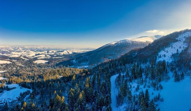ピリペットの村の近くのウクライナの雪と澄んだ青い空に覆われたカルパティア山脈の素晴らしい風景。