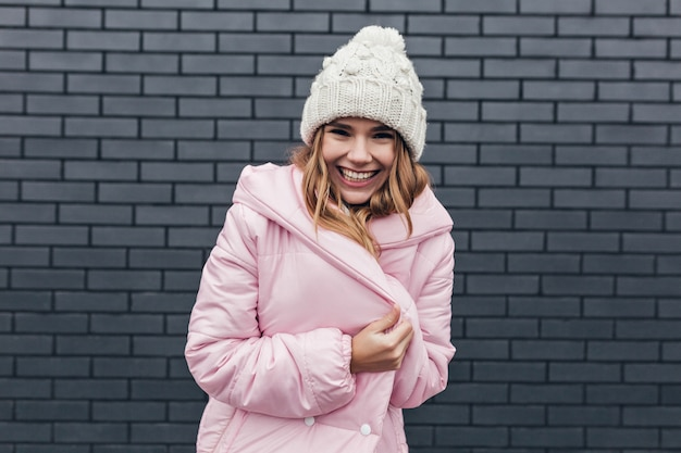 Замечательная смеющаяся девушка позирует в розовом пальто. открытое фото возбужденной блондинки в модной зимней шапке.