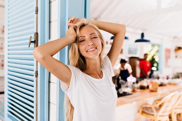 ポジティブな笑顔でポーズをとるレトロなジーンズの素晴らしい日焼けした女性。 無料写真