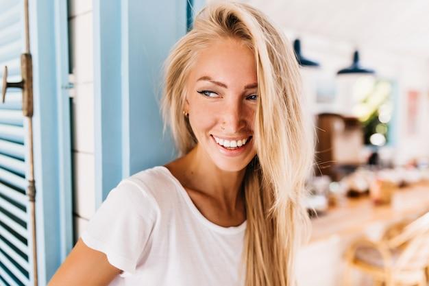 Meravigliosa donna leggermente abbronzata in jeans retrò in posa con un sorriso positivo.