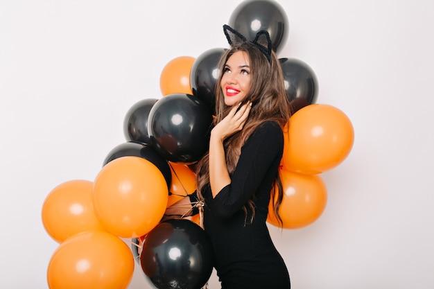 Meravigliosa donna dai capelli lunghi in posa sognante con palloncini di halloween