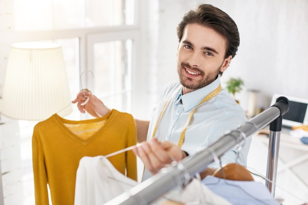 멋진 모습. 기쁜 수염을 가진 스타일리스트가 웃고 그의 컬렉션에서 스웨터를보고