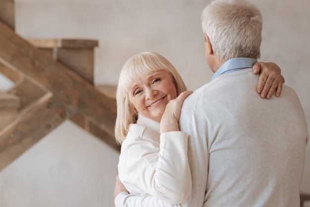 Wonderful mood. delighted happy senior woman smiling and hugging her husband while looking at you