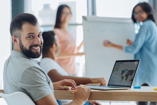 Wonderful mood. happy intelligent bearded man sitting in front of the laptop and smiling to you while attending a professional training seminar